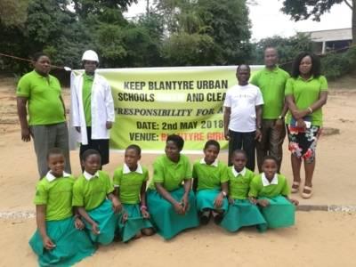 Gruppenbild mit Organisatorinnen und Organisatoren, Schulkindern und dem stellvertretendne Bürgermeister der Stadt Blantyre vor einem Plakat.