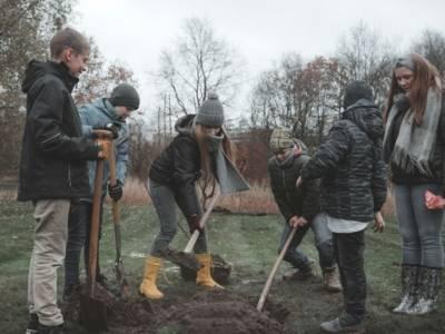 Kinder buddeln auf dem Gelände der Concordia-Versicherung ein Loch, um einen Baum zu pflanzen.