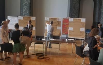 Gäste des Agenda-Plenums diskutieren über die Ergebnisse, die an Moderationswänden aushängen.