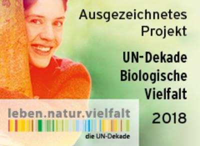 """Auf dem Logo """"Ausgezeichnetes Projekt UN-Dekade Biologische Vielfalt 2018"""" ist neben dem Schrifzug eine Frau zu sehen, die einen Baum umarmt."""