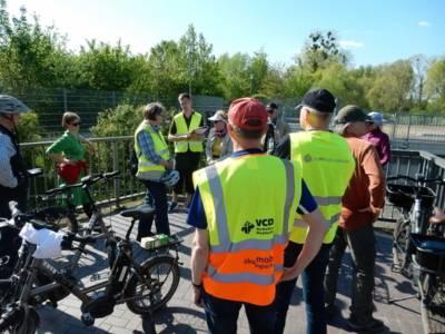 Personen mit Elektrofahrrädern und Tourleiter in gelben Warnwesten mit Aufschrift VCD und Stattreisen