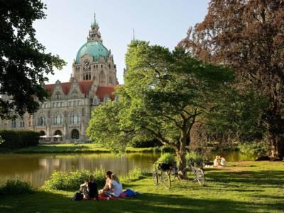 Eine Gruppe von Personen, die mit Fahrrädern unterwegs sind, picknickt auf dem Rasen am Maschteich mit Blick auf das Neue Rathaus von Hannover