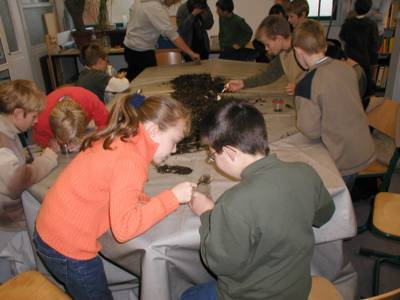 Schülerinnen und Schüler untersuchen Kompost mit der Lupe