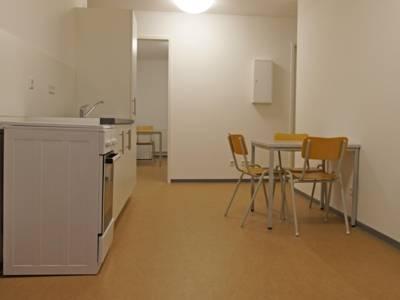 Eine Kochnische, davor ein Tisch mit drei Stühlen.