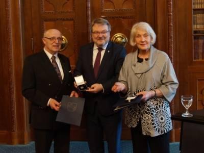 Zwei Männer und eine Frau mit Auszeichnungen.