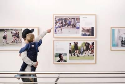 Sportlehrer Fabian Perske zeigt seinem Sohn bei der Ausstellungseröffnung im Freizeitheim Vahrenwald die Bilder der Ausstellung Beweggründe I.