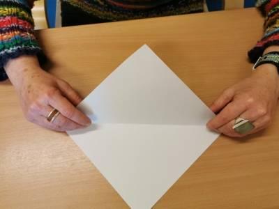 Eine Person faltet ein Blatt Papier zu einem Dreieck.