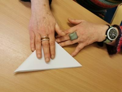 Eine Person faltet ein bereits gefaltetes Blatt Papier.