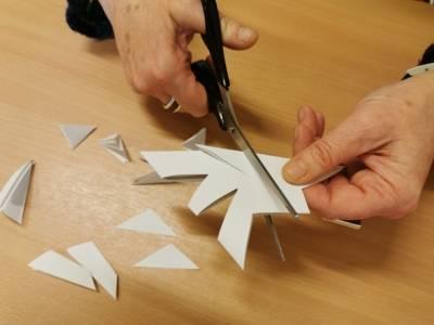 Eine Person schneidet Muster in ein gefaltetes Blatt Papier.