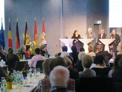 Eine Gesprächsrunde von drei Männern und einer Frau auf einem Podium, davor sitzt an langen Tischen das Publikum. Im Hintergrund sind sechs Flaggen zu sehen, unter anderem die europäische, die rumänische und die deutsche.