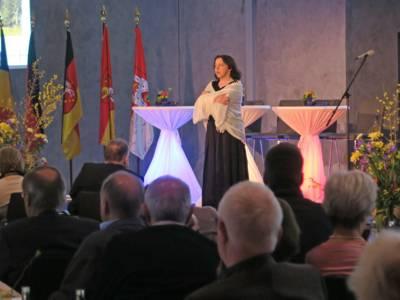 Eine Schauspielerin auf der Bühne rezitiert mit verschränkten Armen. Im Hintergrund fünf unterschiedliche Flaggen, im Vordergrund das Publikum, das sitzend dem Vortrag zuschaut.