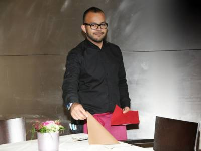 Junger Mann beim Eindecken eines festlich dekorierten Tisches