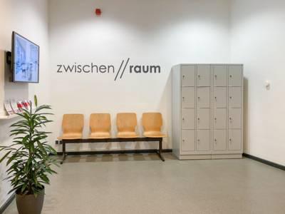 Eine Bank mit vier Stühlen, ein Schrank und ein Monitor in einem Raum.