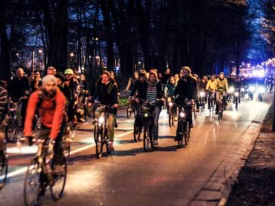 Viele Radfahrer auf einer Straße in der Nacht.