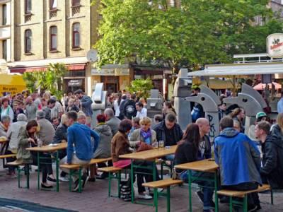 Viele Menschen stehen an einem Platz oder sitzen auf Bänken an Tischen und trinken und essen.
