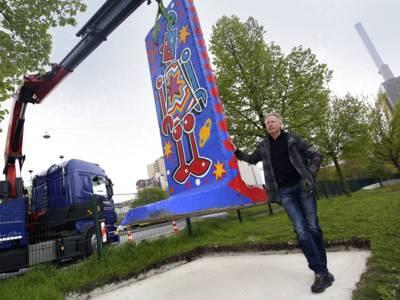 Per Kran wird ein bunt bemaltes Stück der Berliner Mauer auf einen Betonsockel gehievt. Davor steht der Künstler Tim Davies.