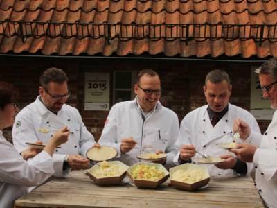 Vier Männer und eine Frau verkosten Kartoffelsalate.