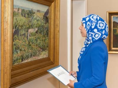 Frau mit Kopftuch in einer Galerie.