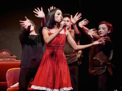 Ein Mädchen singt, im Hintergrund tanzen weitere Kinder.