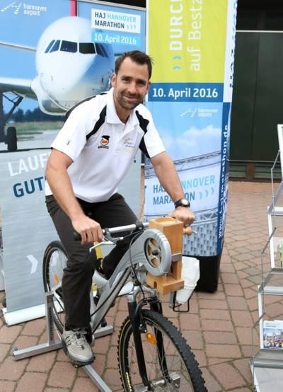 Mann sitzt auf einem Fahrrad, an dem eine Getreidemühle befestigt ist.