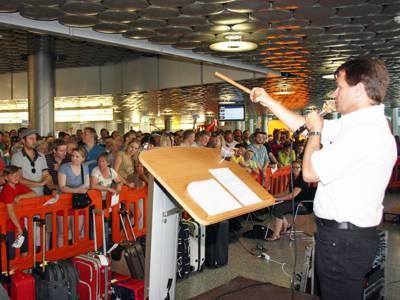 Mann mit Holzhammer steht an einem Pult. Davor sind Koffer und Reisetaschen sowie hinter einer Absperrung viele Zuschauer in einem Flughafenterminal.