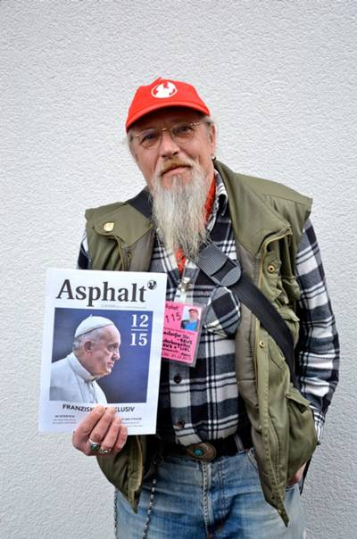 Ein Mann mit Bart und Baseballcap hält ein Magazin in der Hand.