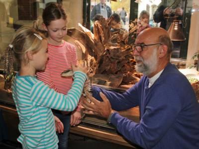 Mann zeigt zwei Kindern ein Tier.