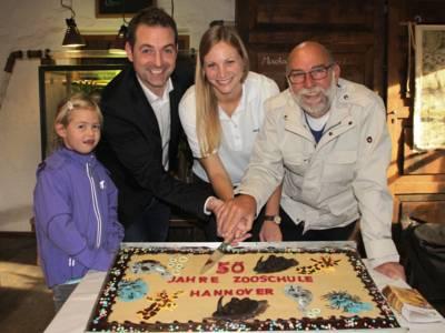 Zwei Männer, eine Frau und ein Mädchen rund um eine Torte, die sie gerade anschneiden.