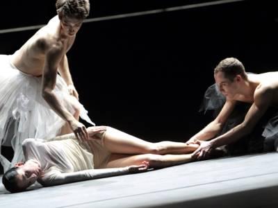 Zwei Balletttänzer um eine Balletttänzerin am Boden.