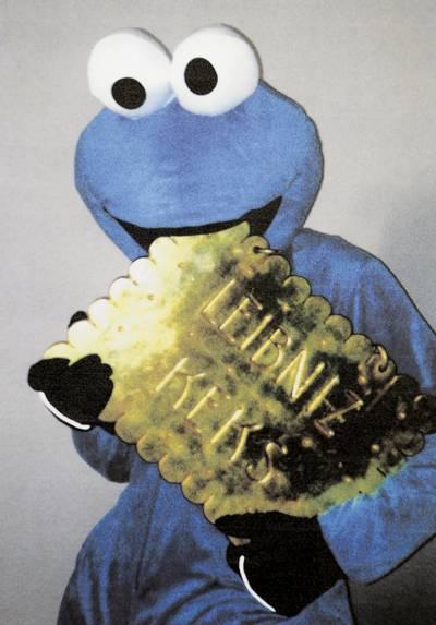 Mensch im Monsterkostüm mit einem goldenen Keks.