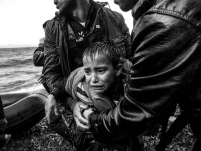 Zwei Helfer ziehen ein weinendes Kind aus einem Gewässer.