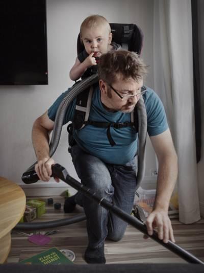 Mann mit Kind auf dem Rücken und Staubsauger in der Hand.