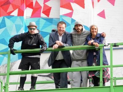 Drei Männer und eine Frau stehen vor einem Graffiti.
