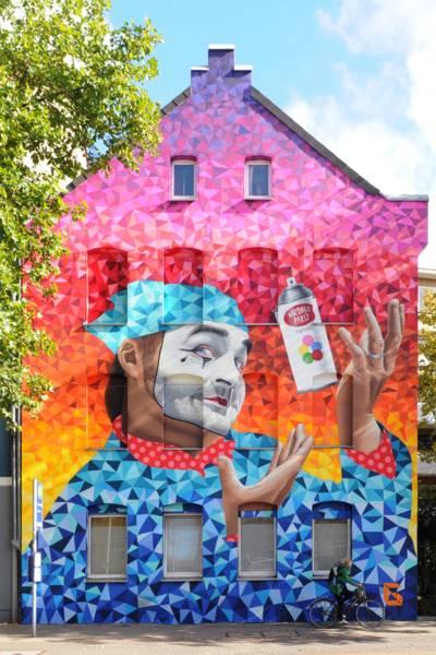 Ein fotorealistischer Clown, mit einer Spraydose jonglierend vor geometrischen Ausdrucksformen.