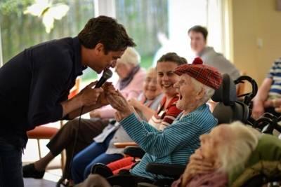 Mann mit Mikrofon sing vor Senioren