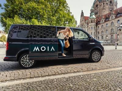 Eine junge Frau steigt vor dem Neuen Rathaus in Hannover aus einem schwarzen Van.