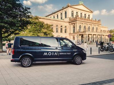 Ein schwarzer Van parkt in Hannover vor dem Operngebäude.