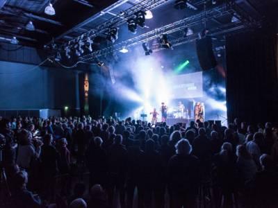 Publikum vor der Bühne eines Konzertsaals.