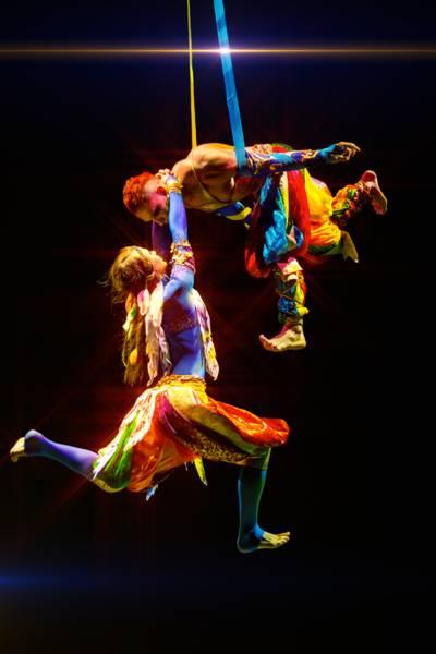 Zwei bunt gekleidete Artisten schweben an Bändern durch die Luft.