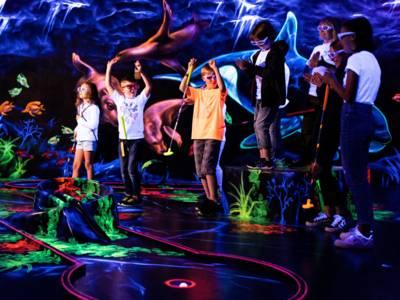 Eine Gruppe von Kindern in einer Minigolf-Halle.