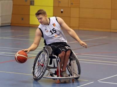 Ein junger Mann im Rollstuhl spielt Basketball