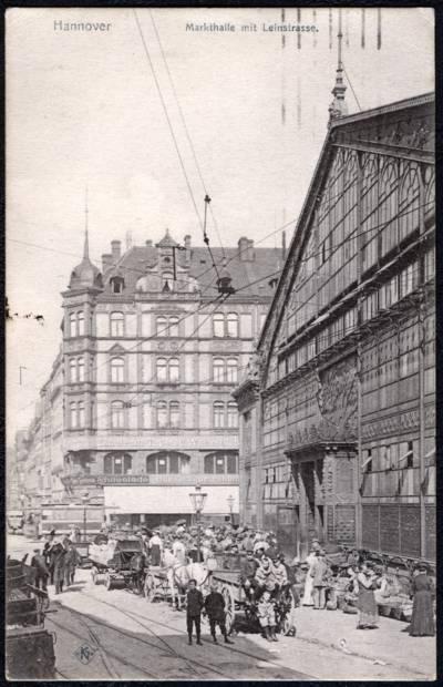 Menschen mit Pferdegespannen vor einem Gebäude an dessen Wand Marktstände aufgebaut sind.