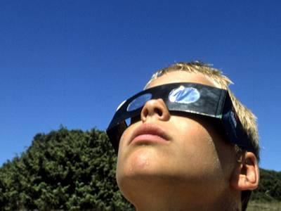 Junge mit Schutzbrille blickt in die Sonne.