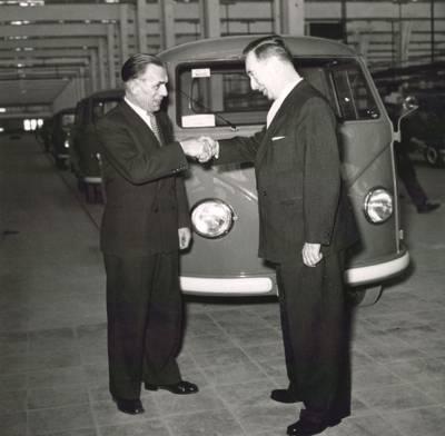 Zwei Männer schütteln sich die Hand vor einem VW Bulli. Historische Schwarz-Weiß-Aufnahme.