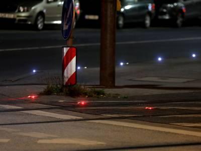 Rote Lichter sind in eine Straße eingelassen.