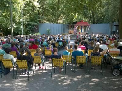Bühne im Wald mit Zuschauern auf Campingstühlen davor