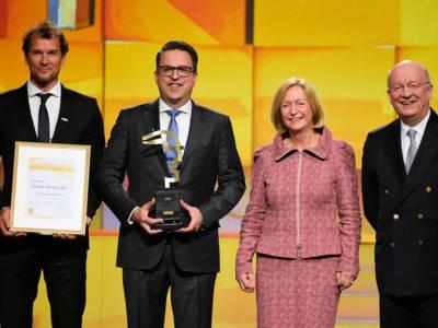 Eine Frau und drei Männer mit Urkunde und Auszeichnung.