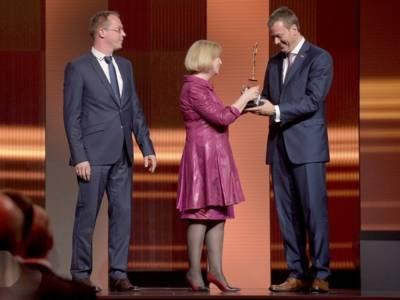 Frau auf Bühne überreicht Preis an zwei Männer