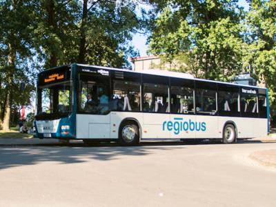 Ein Bus mit der Aufschrift regiobus stehend aus Front-/Seitenansicht, im Hintergrund eine Grünflache mit See.