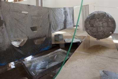 Installation in einem Raum: Auf einer Leine hängt tropfnasse Wäsche, auf dem Boden stehen mit Wasser gefüllte Behälter, auch der Boden selbst ist nass.
